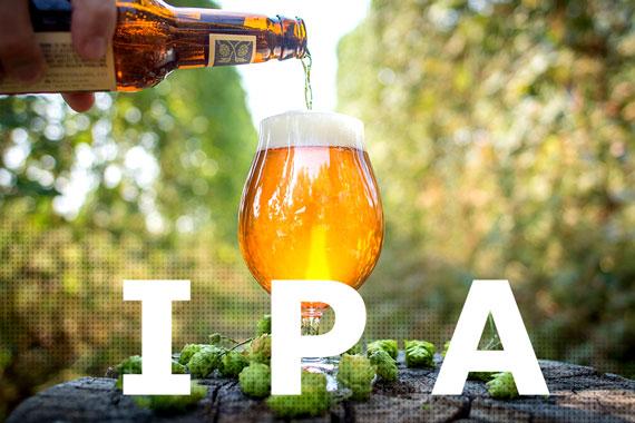 Bottiglia che versa birra bionda in un bicchiere, coni di luppolo sparsi su un tavolo e scritta IPA bianca in primo piano